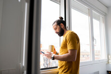 Handsome Man Using Smart Phone While Standing Near Window At Home