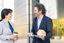 Smiling Male Real Estate Agent With House Model Discussing With Female Customer Holding Disposable Cup In Park