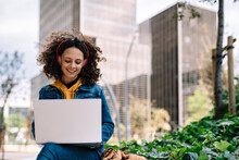 Smiling Woman With Wireless Headphones Working On Laptop In City