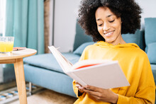 Young Woman Reading Book While Sitting At Home
