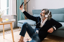 Man With Headphones Taking Selfie Through Smart Phone While Sitting On Floor At Home