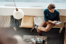 Mature Man Using Digital Tablet Sitting At Coffee Shop