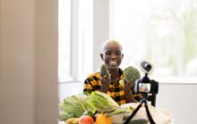 Smiling Female Influencer Showing Vegatbles While Vlogging Using Video Camera At Home