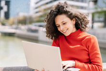 Smiling Young Woman Using Laptop By Railing During Sunny Day