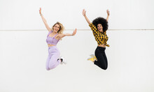 Cheerful Female Friends Jumping By Wall Outdoors