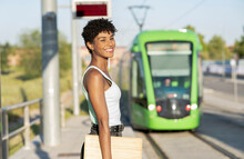 Young Woman Waiting For Tram At Station During Sunny Day