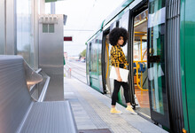 Afro Woman Holding Laptop While Entering In Train At Railroad Station