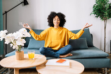 Young Woman Meditating While Sitting On Sofa At Home