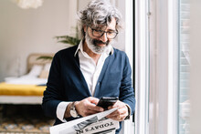 Smiling Senior Man With Newspaper Using Smart Phone Near Window At Home