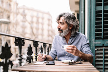 Senior Man Having Coffee Writing In Note Pad While Looking Away In Balcony At House