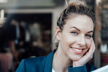 Smiling Mid Adult Businesswoman With Hand On Chin In Coffee Shop