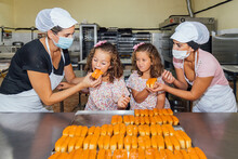 Women Wearing Protective Face Mask Feeding Pastry To Twin Girls In Bakery Kitchen