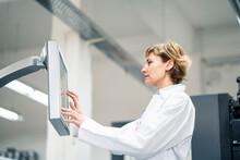 Technician Wearing Lab Coat Operating Printing Machine In Laboratory