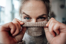 Playful Woman Covering Face In Sweater At Cafe