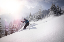 Man Moving Down From Snowy Mountain While Skiing During Winter