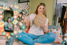 Female Influencer Showing Like And Subscribe Cardboard While Vlogging Through Mobile Phone At Home