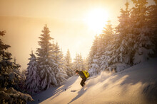 Mid Adult Man Skiing On Snowy Mountain During Sunrise
