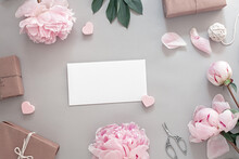 Festive Composition With Pink Peony Flowers, Gifts, Scissors, Blank White Sheet In The Center, Top View And Flat Lay, Floral Frame, Copy Space