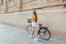 Young Woman Looking Away While Wheeling Bicycle By Stone Wall