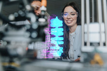 Smiling Female And Male Engineers Examining Futuristic Automation At Laboratory