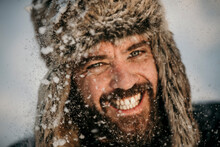 Mid Adult Man Wearing Hunters Cap Smiling While Snowing