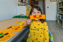 Cute Girl Holding Smiling Emoticon While Playing At Home