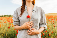 Woman Holding Red Poppy Flower While Standing At Field
