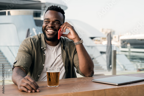 Fotografie, Obraz Young african man drinking beer at brewery bar using mobile phone with luxury ya
