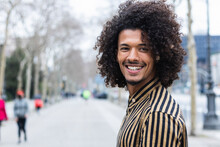 Young Man With Curly Hair Looking Away On Footpath