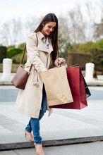 Smiling Woman Searching In Shopping Bag While Moving Down From Stairs