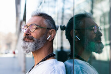 Hipster Man With Eyes Closed In Front Of Glass