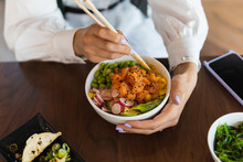 Young Woman Eating Poke Bowl With Chopsticks On Table At Restaurant