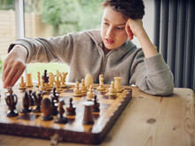Intelligent Boy Playing Chess At Home