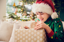 Cute Boy In Santa Hat Unwrapping Gift During Christmas At Home