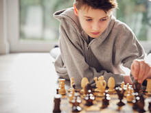 Dedicated Boy Playing Chess At Home