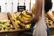 Woman Choosing Bananas At Grocery Store
