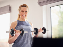 Smiling Woman Holding Weights While Exercising At Home