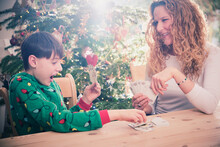 Smiling Mother Looking At Son While Playing Cards During Christmas At Home