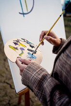 Woman Mixing Colors With Paintbrush While Painting