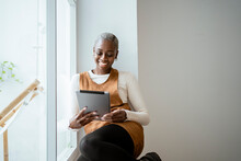 Smiling Woman Looking At Digital Tablet While Sitting By Window In Living Room