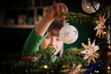 Boy Decorating Christmas Tree With Ornaments At Home