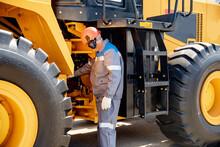 Professional Mechanic Checks Hydraulic Hose System Equipment On Excavator To Raise Bucket
