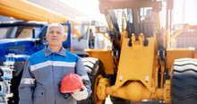 Excavator Driver In Hard Hat Stands At Construction Equipment, Concept Banner Industrial Man Portrait
