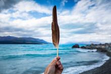 New Zealand, Canterbury, Hand Holding Feather With Lake Tekapo In Background