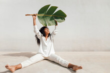 Young Woman With Eyes Closed Holding Banana Leaf Sitting In Front Of White Wall During Sunny Day