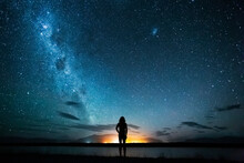New Zealand, Canterbury, Twizel, Silhouette Of Man Looking At Lake Poaka Under Starry Sky