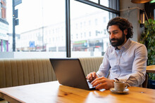 Handsome Businessman Using Laptop While Sitting At Desk In Office