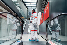 Smiling Male Astronaut Looking Over Shoulder While Standing By Escalator