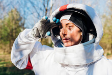Female Astronaut Saluting While Looking Away On Sunny Day