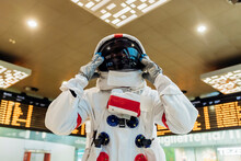 Male Astronaut Wearing Space Helmet While Standing At Arrival Departure Board